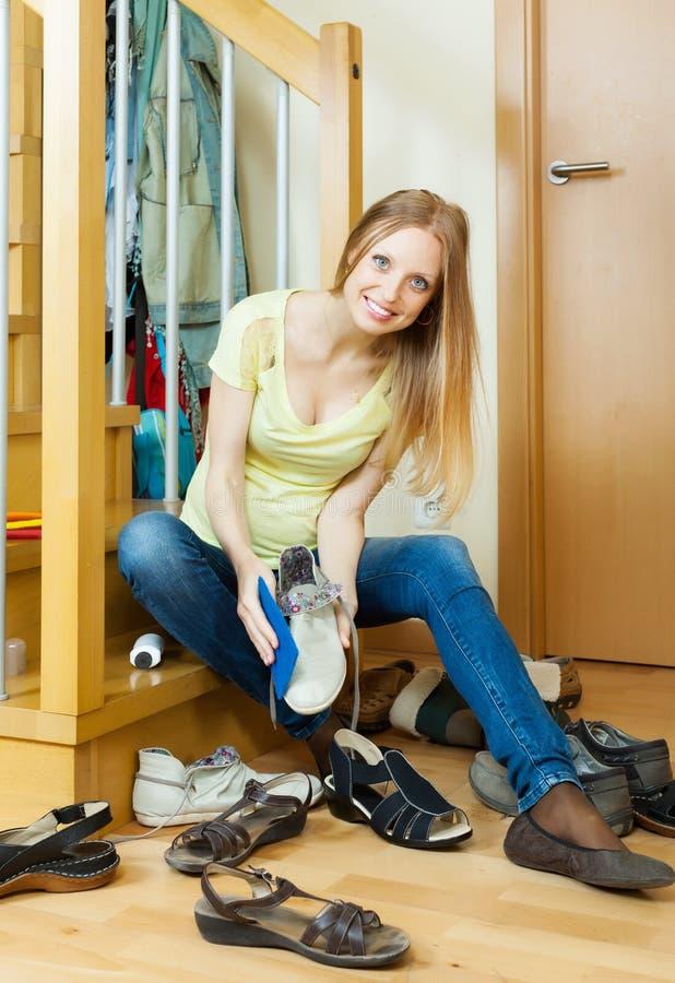 Glückliche blonde Hausfraureinigungsschuhe lizenzfreies stockbild