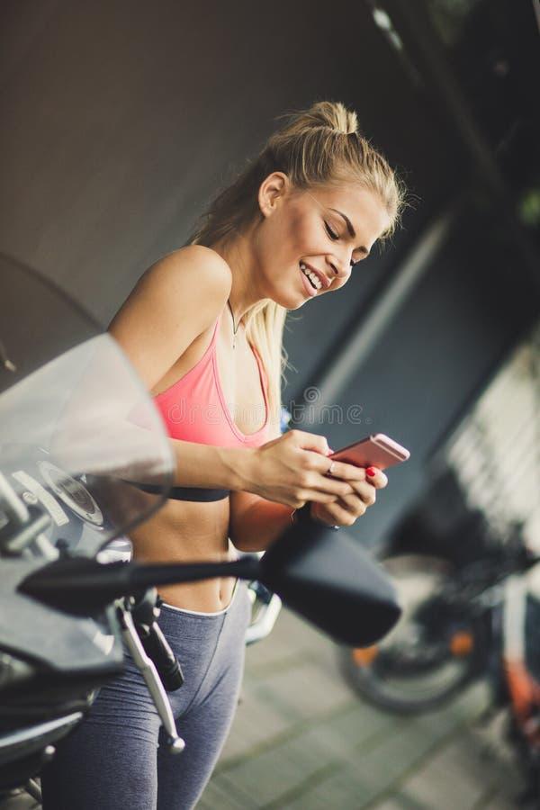 Glückliche blonde junge Frauen, die ihr intelligentes Telefon verwenden lizenzfreie stockbilder