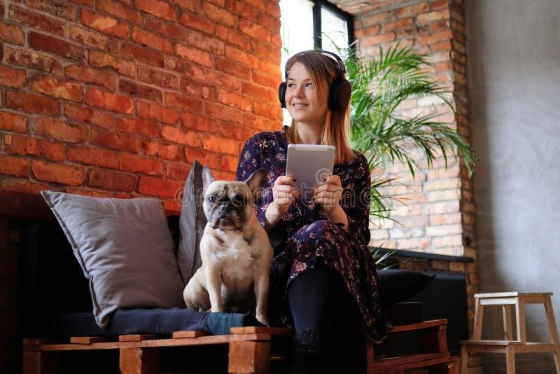 Glückliche Blondine in einem Kleid halten Tablette und das Hören Musik beim Sitzen mit ihrem netten Pug auf Sofa stockbilder