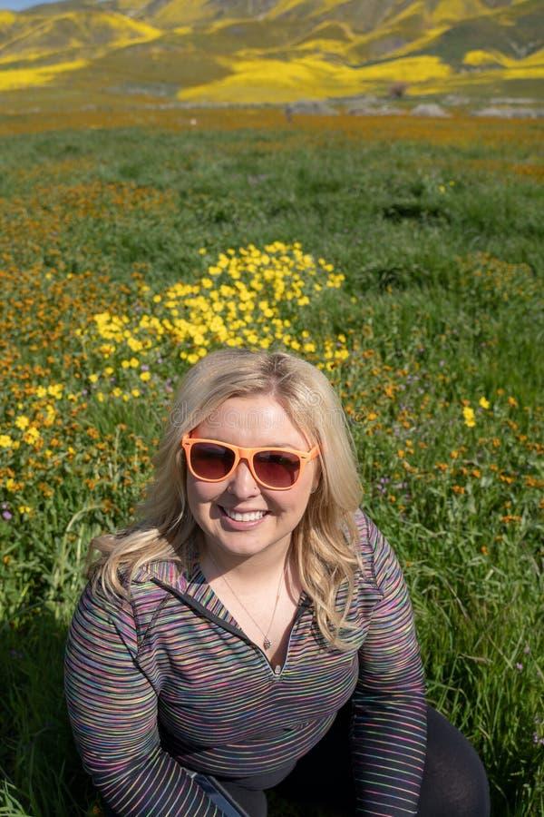 Gl?ckliche Blondine werfen mit Wildflowers im einfachen Nationaldenkmal Carrizo auf lizenzfreie stockfotografie