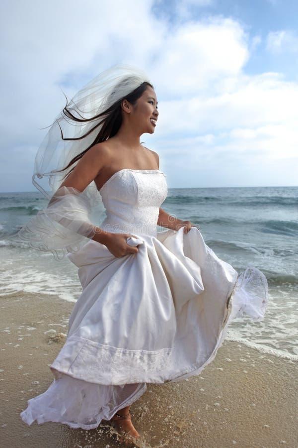 Glückliche Braut auf dem Strand gehend in den Ozean stockbild