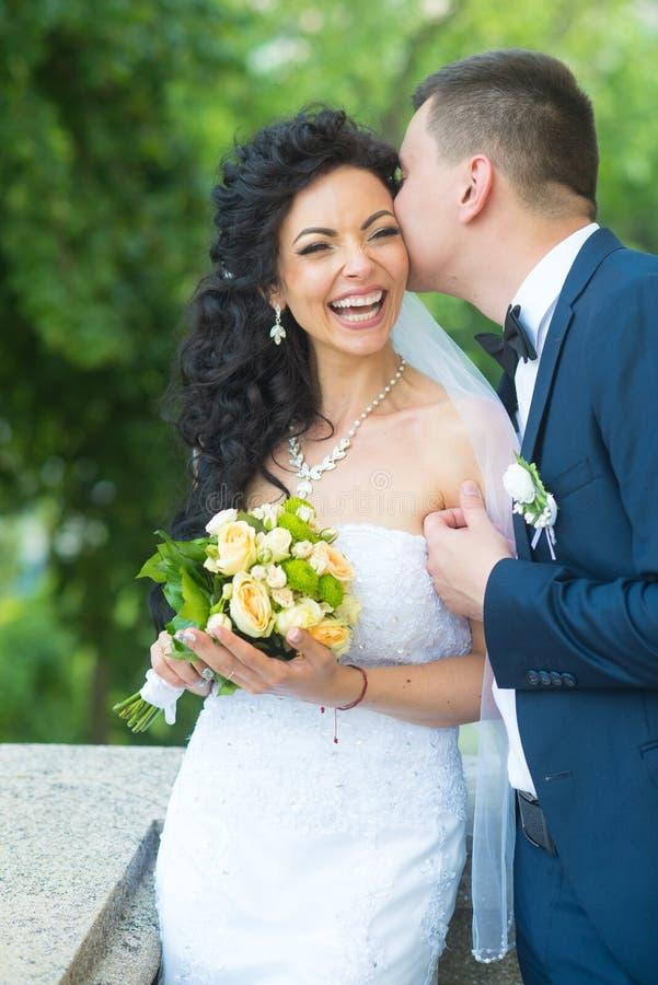 Glückliche Braut des Bräutigamkusses mit Blumenstrauß Frauen- und Mannlächeln am Hochzeitstag Hochzeitspaare in der Liebe Jungver stockbilder