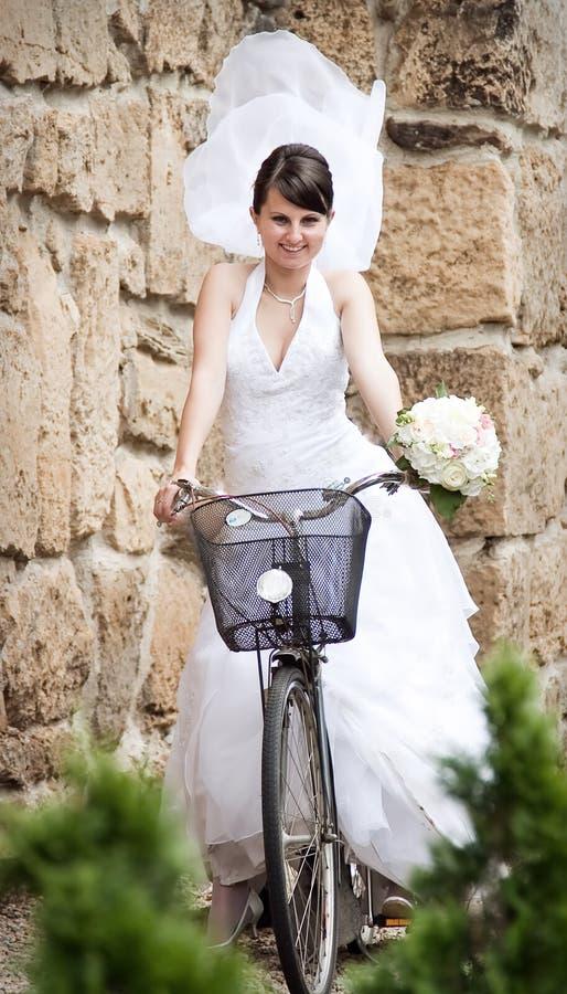 Glückliche Braut, die ein Fahrrad reitet lizenzfreies stockbild