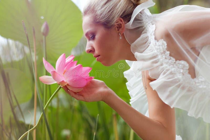 Glückliche Braut, die einen Lotos riecht stockbild