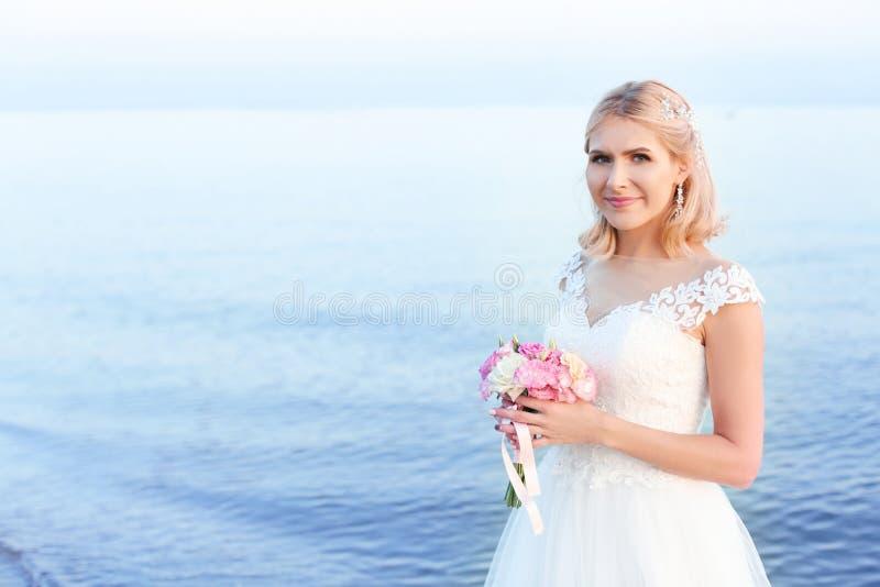 Glückliche Braut, die Hochzeitsblumenstrauß auf Strand hält stockfotografie