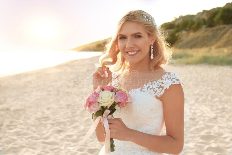 Glückliche Braut, die Hochzeitsblumenstrauß hält stockbild