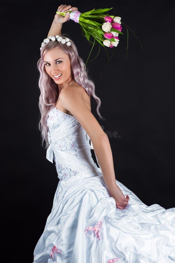Glückliche Braut, die mit einem Blumenstrauß von Tulpen läuft lizenzfreie stockfotos