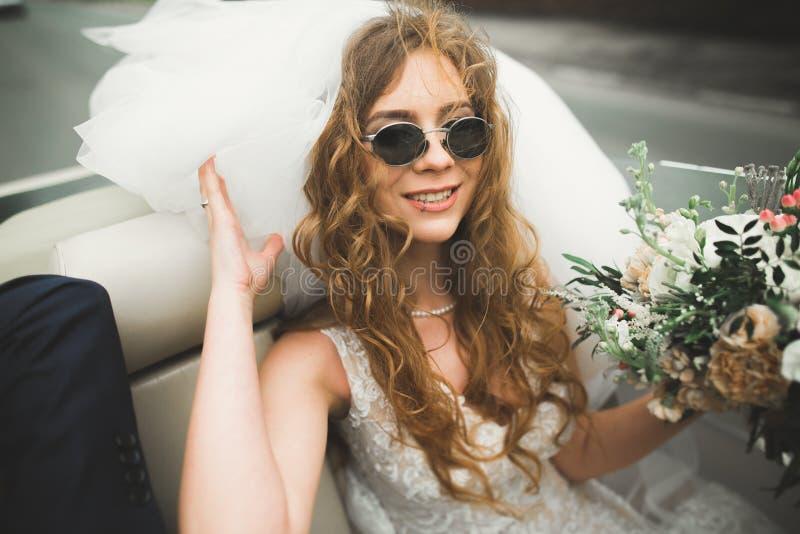 Glückliche Braut im Retro- Auto, das an ihrem Säuberntag aufwirft lizenzfreies stockbild
