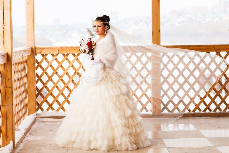 Glückliche Braut mit Blumenstraußwartebräutigam im Winterhochzeitstag lizenzfreie stockfotografie