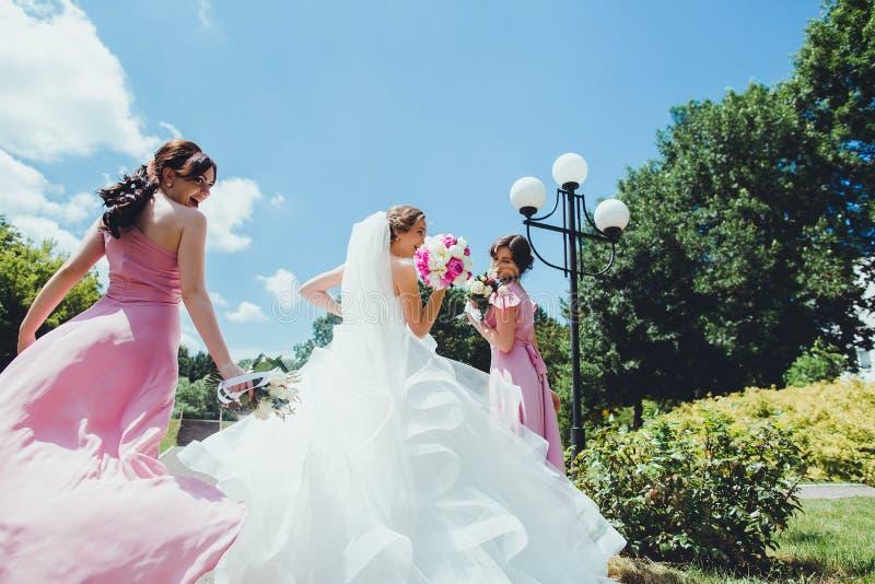Glückliche Braut mit Brautjungfern im Park am Hochzeitstag lizenzfreie stockbilder