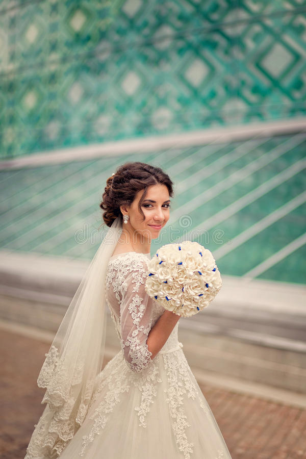 Glückliche Braut mit ungewöhnlichem Blumenstrauß auf dem Hintergrund des modernen Glasgebäudes stockbilder