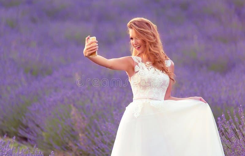 Glückliche Braut nehmen ein selfie mit ihrem Telefon auf dem Lavendelgebiet lizenzfreie stockfotografie