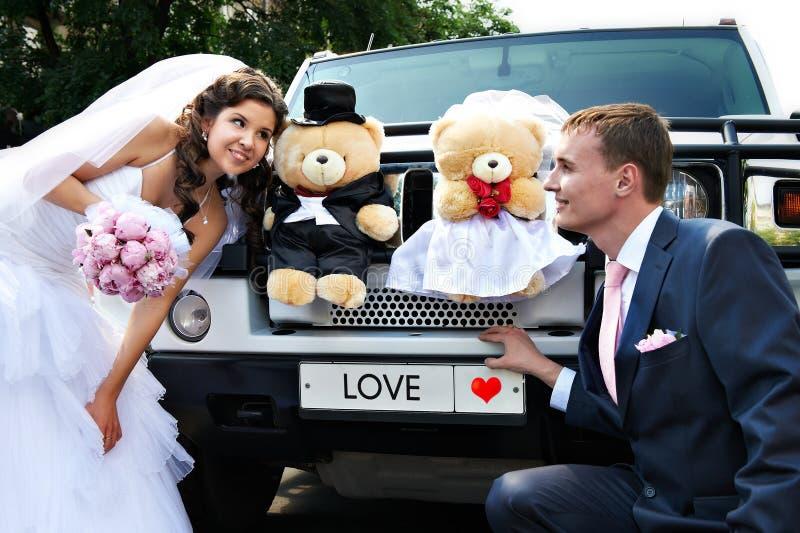 Glückliche Braut und Bräutigam über Hochzeitslimousine stockbilder
