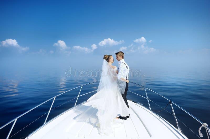 Glückliche Braut und Bräutigam auf einer Yacht lizenzfreie stockfotografie