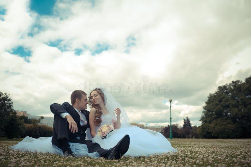 Glückliche Braut und Bräutigam auf ihrer Hochzeit in einem Park lizenzfreie stockfotos