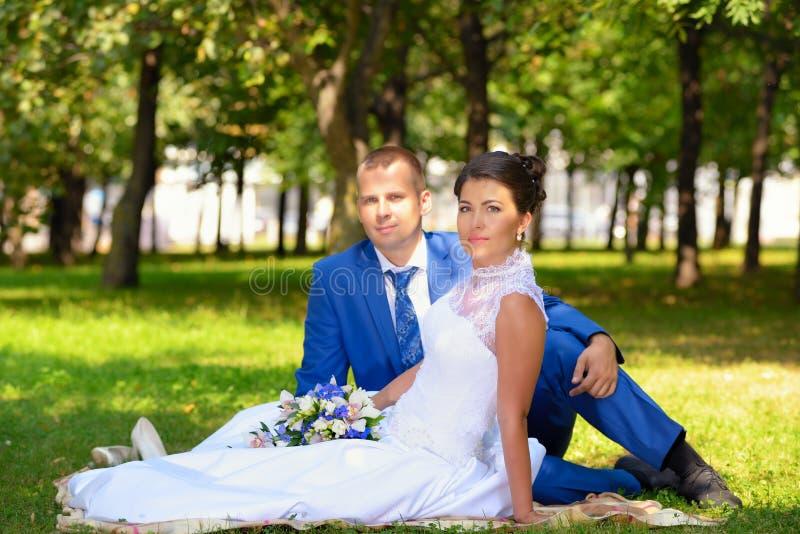 Glückliche Braut und Bräutigam auf ihrer Hochzeit sitzt auf dem Gras im Park stockbilder