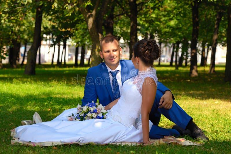 Glückliche Braut und Bräutigam auf ihrer Hochzeit sitzt auf dem Gras im Park lizenzfreie stockbilder