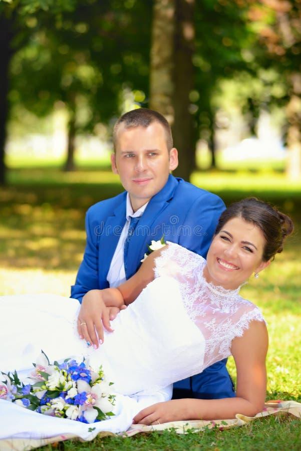 Glückliche Braut und Bräutigam auf ihrer Hochzeit sitzt auf dem Gras im Park lizenzfreie stockfotos