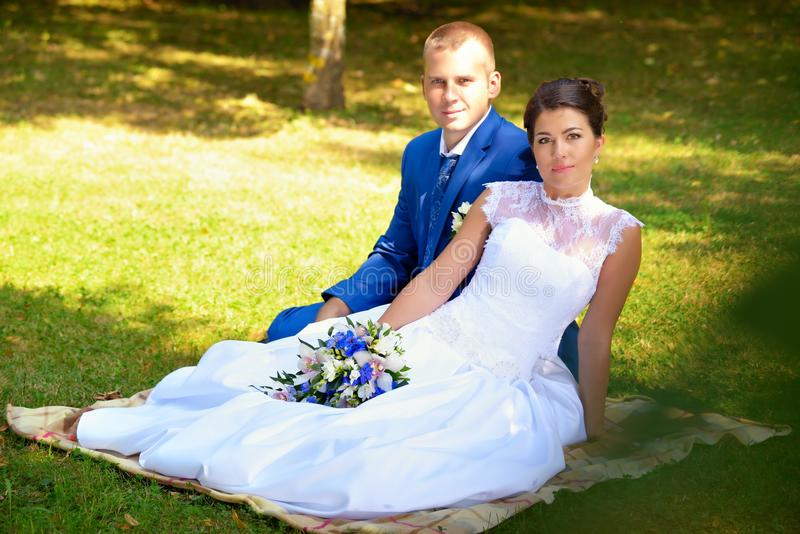 Glückliche Braut und Bräutigam auf ihrer Hochzeit sitzt auf dem Gras im Park lizenzfreies stockbild