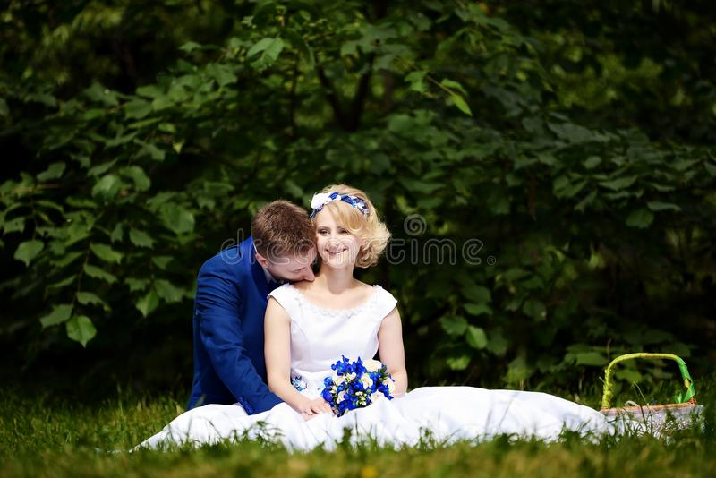 Glückliche Braut und Bräutigam auf ihrer Hochzeit sitzt auf Gras im Park stockfotos