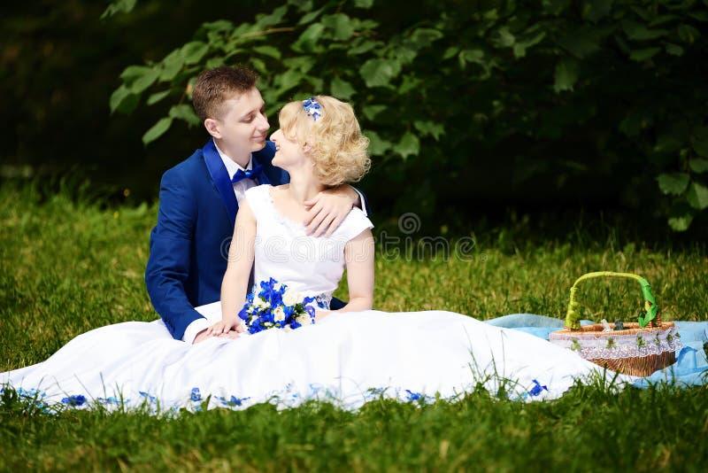 Glückliche Braut und Bräutigam auf ihrer Hochzeit sitzt auf Gras im Park lizenzfreie stockfotos