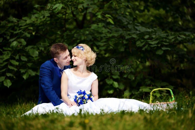 Glückliche Braut und Bräutigam auf ihrer Hochzeit sitzt auf Gras im Park lizenzfreie stockbilder
