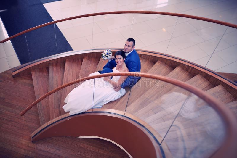 Glückliche Braut und Bräutigam auf ihrer Hochzeit stehen auf einer hölzernen Leiter stockbild