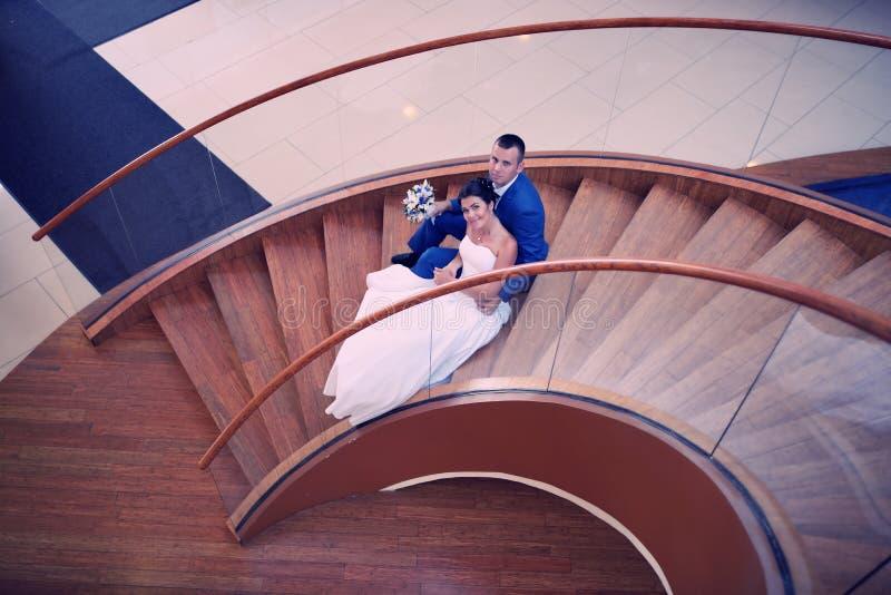 Glückliche Braut und Bräutigam auf ihrer Hochzeit stehen auf einer hölzernen Leiter lizenzfreies stockfoto