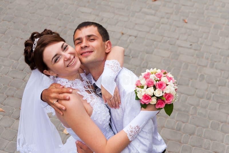 Glückliche Braut und Bräutigam an der Hochzeit gehen stockfotografie