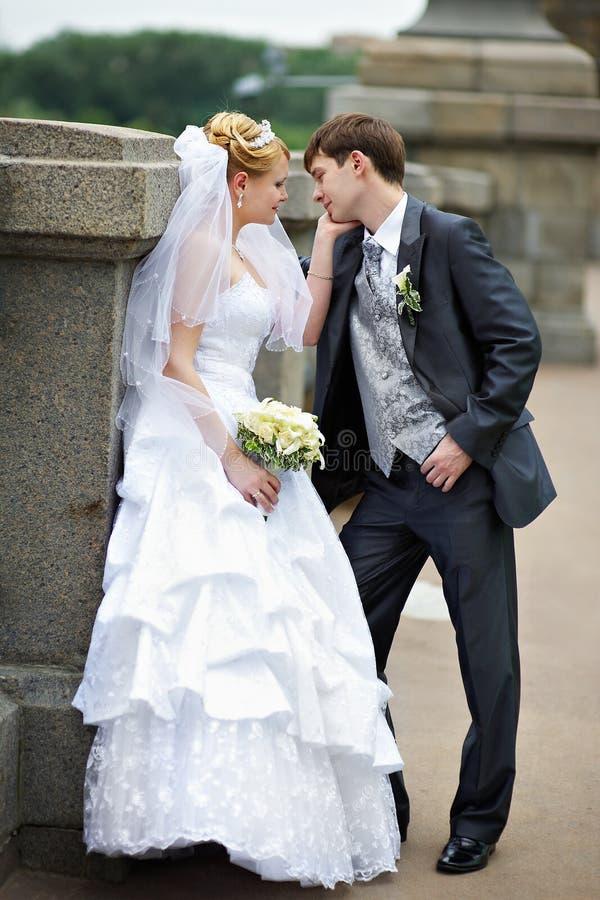 Glückliche Braut und Bräutigam an der Hochzeit gehen auf Brücke stockbild