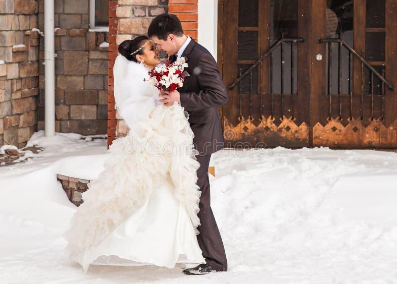Glückliche Braut und Bräutigam des romantischen Kusses am Winterhochzeitstag stockfotos