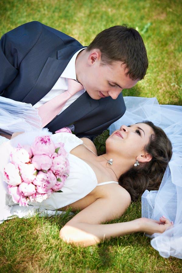 Glückliche Braut und Bräutigam, die auf Gras liegt lizenzfreie stockbilder