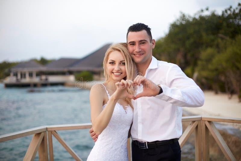 Glückliche Braut und Bräutigam, die an das Herzzeichen mit ihren Händen auf einem tropischen Strand des Luxuskurorts lächelt und  stockbild
