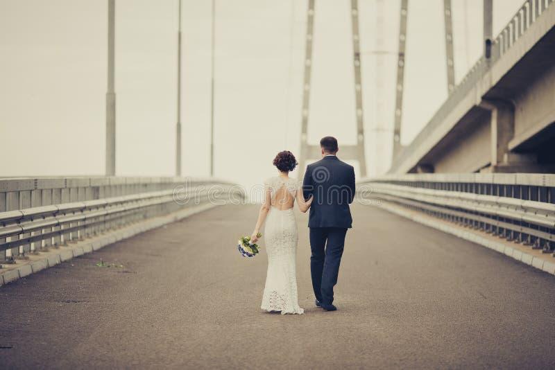 Glückliche Braut und Bräutigam, die Hochzeitstag feiert Verheiratetes Paar, das auf Brücke weggeht Langes Familienleben-Straßenko stockfoto