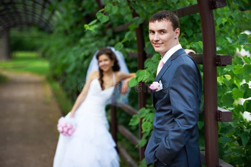 Glückliche Braut und Bräutigam, die im Bogen steht stockfotos
