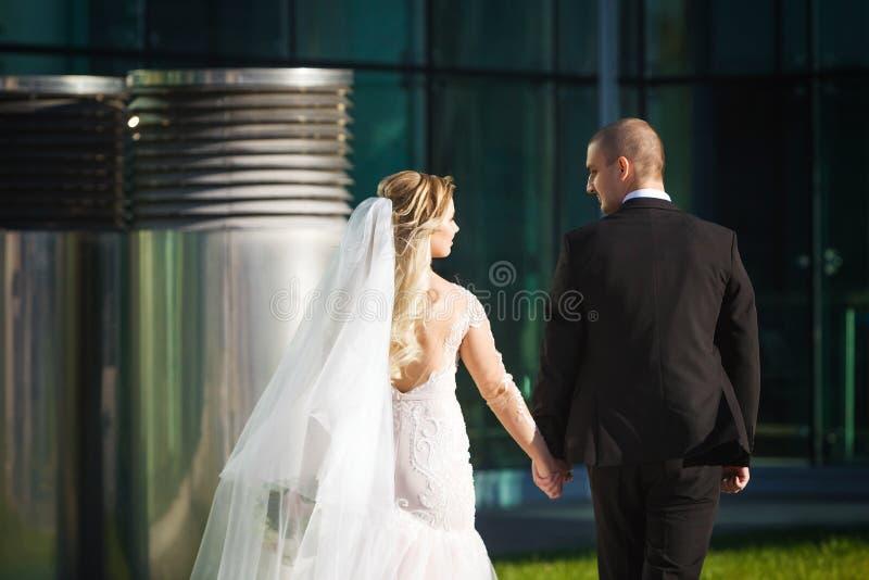 Glückliche Braut und Bräutigam, die nahe dem modernen Gebäude geht lizenzfreie stockbilder