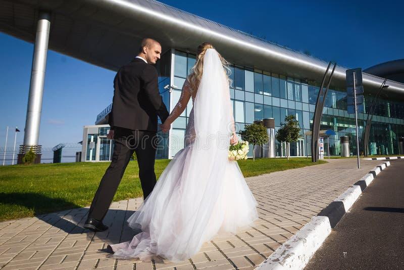 Glückliche Braut und Bräutigam, die nahe dem modernen Gebäude geht stockfoto