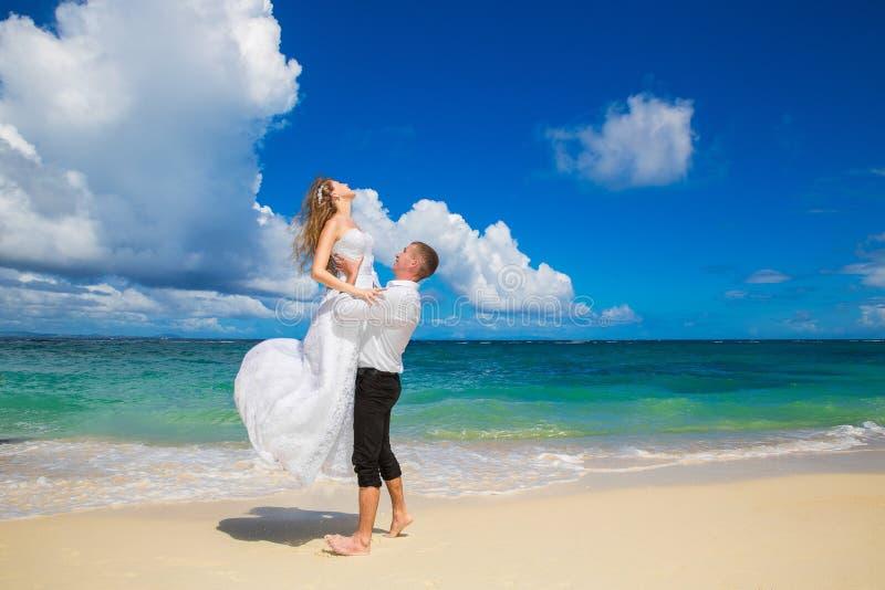 Glückliche Braut und Bräutigam, die Spaß auf einem tropischen Strand hat Heirat stockbild