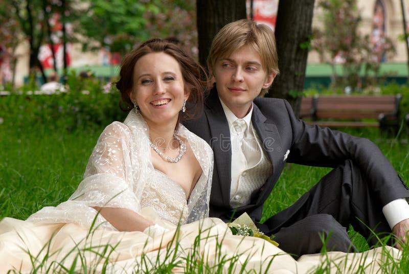 Glückliche Braut und Bräutigam, die zusammen auf den gras sitzt lizenzfreies stockfoto