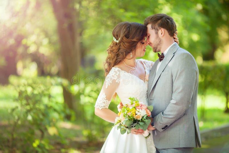Glückliche Braut und Bräutigam an einem Park an ihrem Hochzeitstag stockbilder