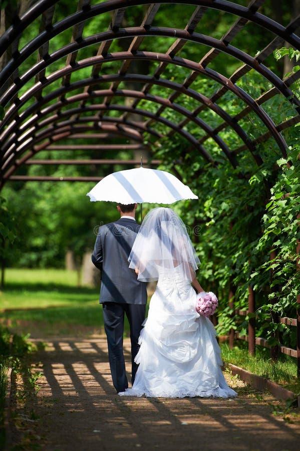 Braut und Bräutigam geht entlang den Bogen stockfoto