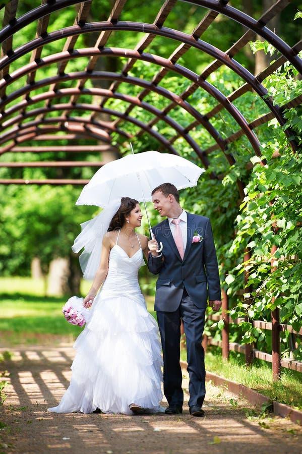 Glückliche Braut und Bräutigam geht entlang den Bogen stockfoto