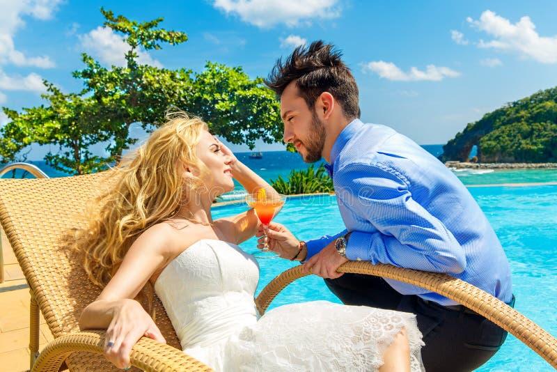 Glückliche Braut und Bräutigam genießen eine Cocktail Poolsideunendlichkeit tropen lizenzfreies stockbild