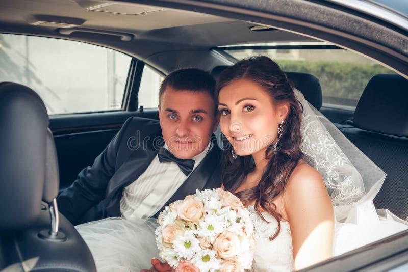 Glückliche Braut und Bräutigam im Auto lizenzfreies stockbild