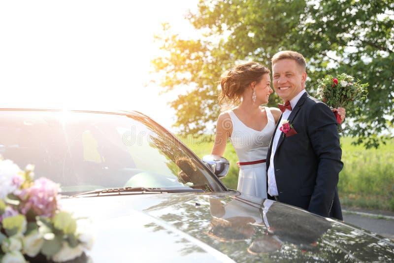 Glückliche Braut und Bräutigam nahe Auto lizenzfreie stockfotos