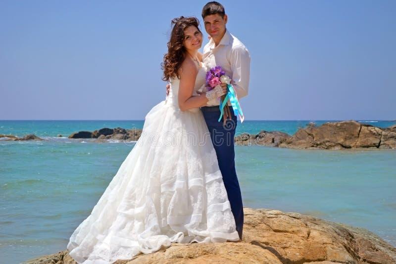 Glückliche Braut und Bräutigam umarmen auf den Felsen im Indischen Ozean Hochzeit und Flitterwochen in den Tropen auf der Insel v lizenzfreies stockbild