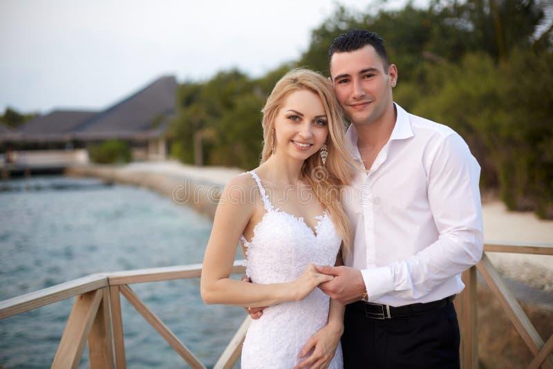Glückliche Braut und Bräutigamlächeln und -Händchenhalten auf einem tropischen Strand des Luxuskurorts auf Malediven Heirat und stockfotografie