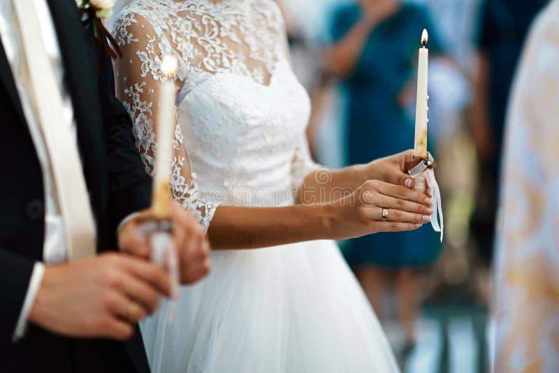 Glückliche Braut und stilvoller Bräutigam, die Kerzenhochzeitszeremonie, Hochzeitspaar am Ehestand in der Kirche, emotionaler Mom stockfotografie
