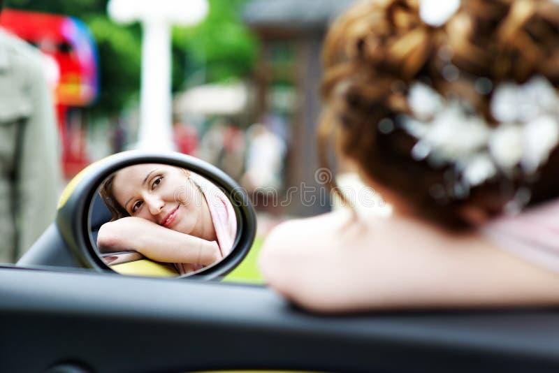 Glückliche Brautblicke im Spiegel des Autos an der Hochzeit gehen lizenzfreies stockfoto