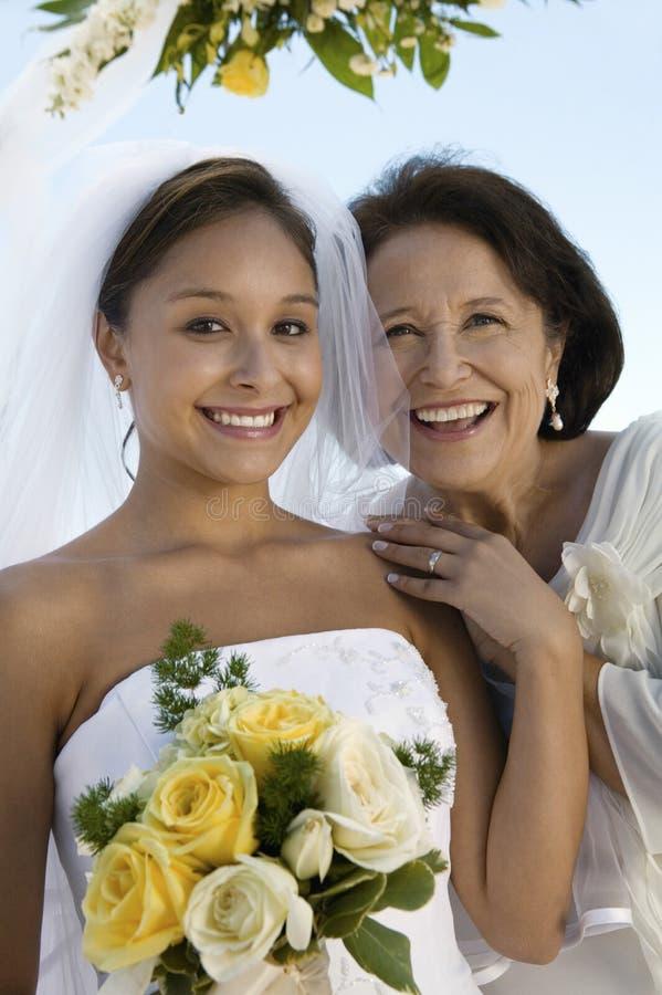Glückliche Brautjungfer und Mutter mit Blumen-Blumenstrauß stockbild